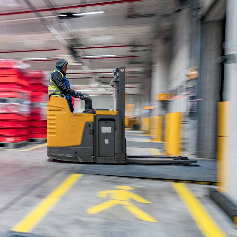 Ein Staplerfahrer bei B+S verlädt Ware am Ladetor. | A forklift driver at B+S loads goods at the loading gate.