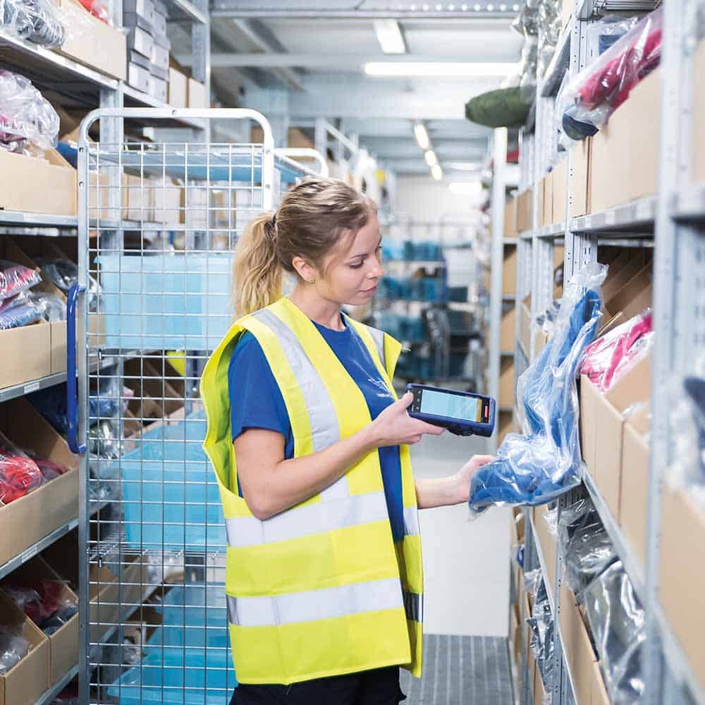 Die qualifizierten Mitarbeiter von B+S machen E-Commerce Fulfillment möglich, wie hier bei der Fachboden-Kommissionierung. | B+S's qualified employees make e-commerce fulfilment possible, as shown here during shelf compartment picking.