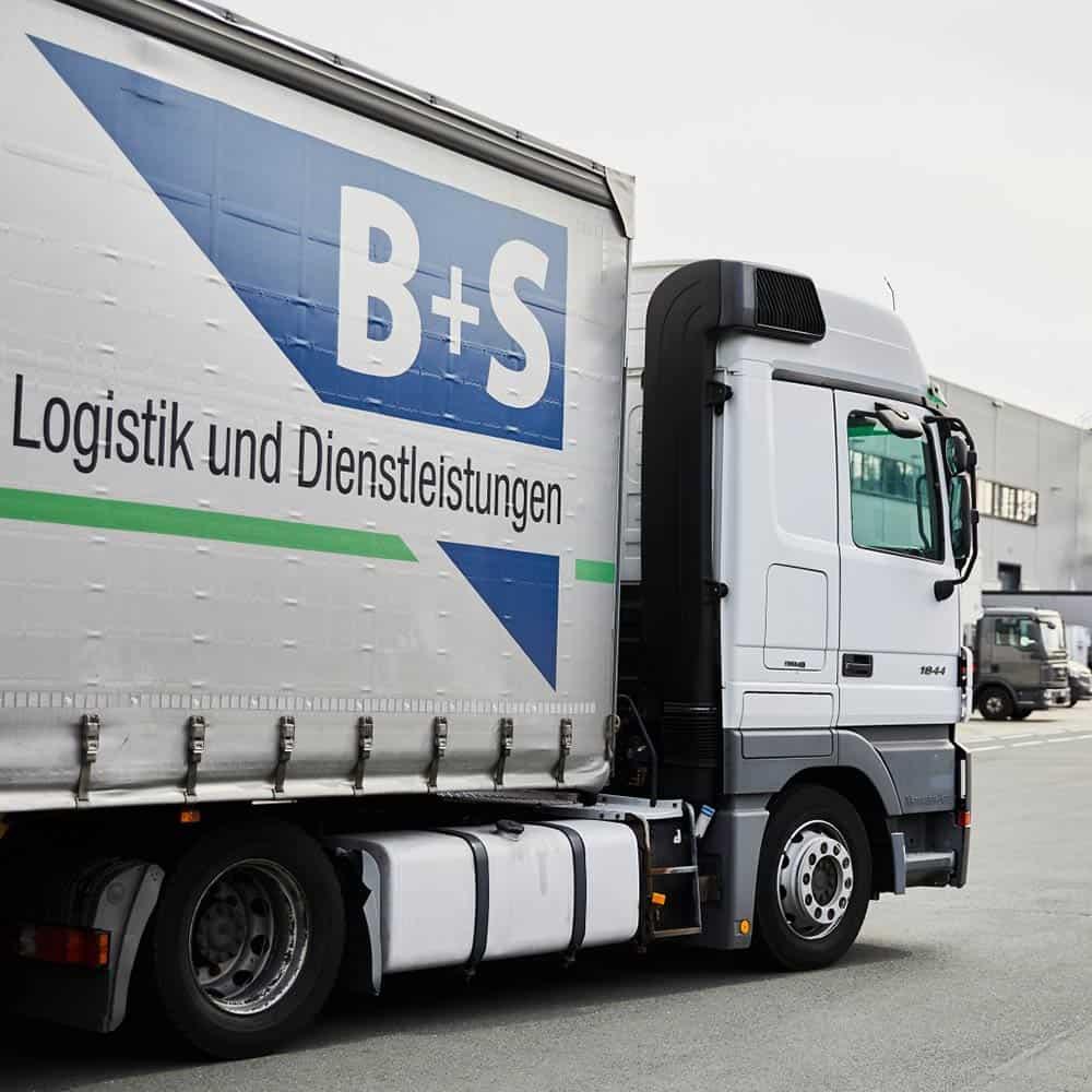 Ein Lkw verlässt den Standort Bielefeld gefüllt mit Waren. | A lorry loaded with goods leaves the Bielefeld site.
