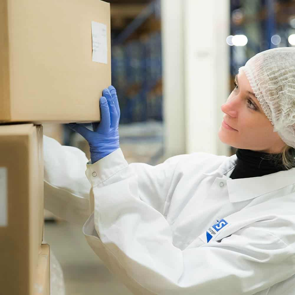 Eine Mitarbeiterin im extra für Pharmalogistik ausgelegten Lager in Zettlitz inspiziert das Etikett eines Kartons. | In the Zettlitz warehouse, which is specially designed for pharmaceutical logistics, an employee inspects the label of a box.