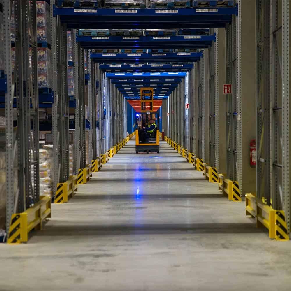 Ein Mitarbeiter fährt mit einem Gabelstapler durch die Gänge des Hochregallagers in Ulm. | An employee drives a forklift through the aisles of the high-bay warehouse in Ulm.