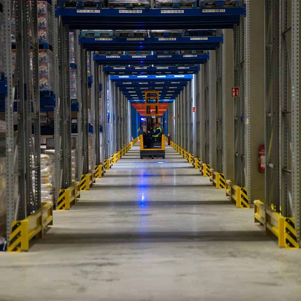 Ein Mitarbeiter fährt mit einem Gabelstapler durch die Gänge des Hochregallagers in Ulm. | An employee drives a forklift through the aisles of the high-bay warehouse in Ulm.